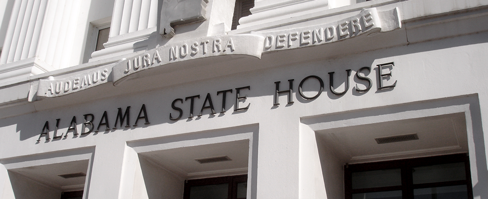 "Photo of the Alabama State House showing the latin phrase ""audemus jura nostra defendere"" in a banner over the words ""Alabama State House"" in all caps"