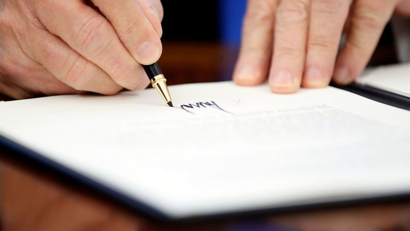 Image of a man holding a felt tip pen and signing a document