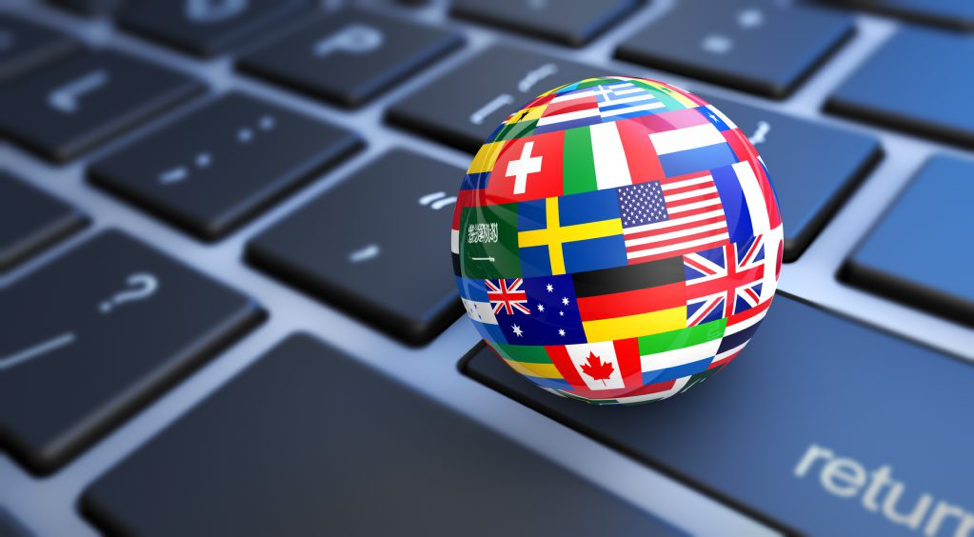 "Image of a keyboard with an orb made up of various countries' flags sitting on the ""return"" key of the keyboard"